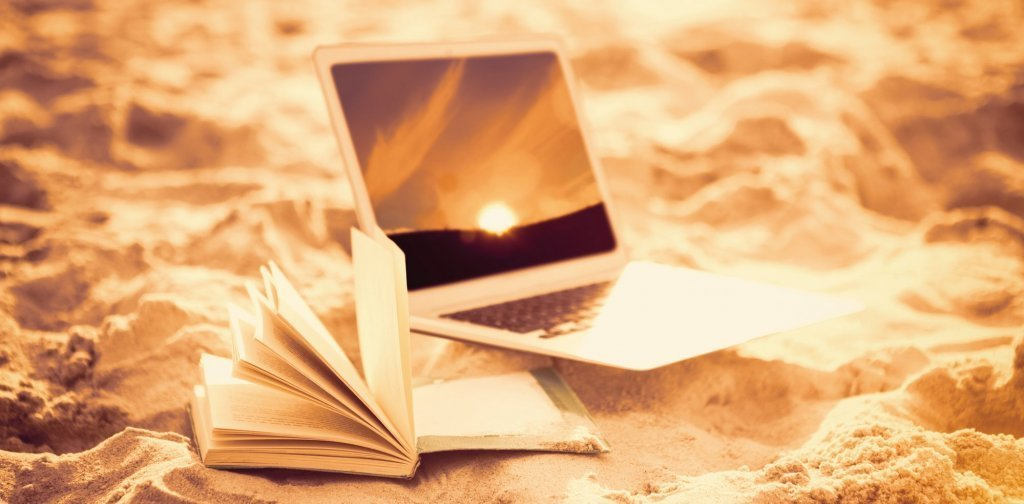 Composite image of open book and laptop on sand at beach